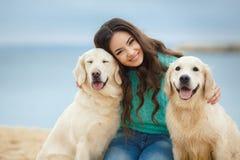 Härlig flicka med hennes hund nära havet arkivbild