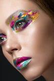 Härlig flicka med idérik färgrik makeup Härlig le flicka royaltyfria bilder