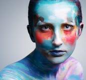 Härlig flicka med idérik färgrik makeup på en grå backgroun royaltyfri bild