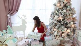 Härlig flicka med julgåvor i ett smart rum stock video