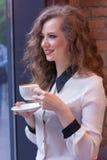 Härlig flicka med kaffe i en vit skjorta Fotografering för Bildbyråer