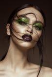 Härlig flicka med kanter för för vårgräsplanmakeup och vampyr Härlig le flicka fotografering för bildbyråer