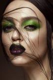 Härlig flicka med kanter för för vårgräsplanmakeup och vampyr Härlig le flicka royaltyfri fotografi