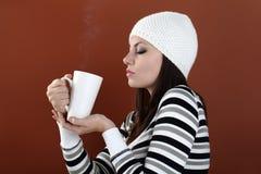 Härlig flicka med koppen i händer som håller den varma drinken Royaltyfria Bilder