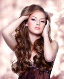 Härlig flicka med långa lockiga hår royaltyfria bilder