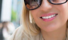 Härlig flicka med långt blont hår och svart le för exponeringsglas Royaltyfria Bilder