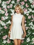 Härlig flicka med långt blont hår som poserar mot blom- bakgrund arkivfoton