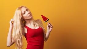 Härlig flicka med långt blont hår som rymmer en stor godis Modeflicka i den röda överkanten som isoleras på gul bakgrund Mode och royaltyfri bild
