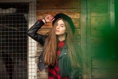 Härlig flicka med långt hår och den svarta hatten, ställningar på bakgrunden av det gamla trähuset för tappning royaltyfri fotografi