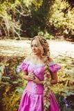 Härlig flicka med långt hår som flätas i en flätad tråd som står av sjön Fotografering för Bildbyråer
