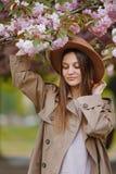 Härlig flicka med långt hår som rymmer den sakura filialen bland rosa körsbärsröda blomningar i vår Modellera bärande stilfull ti royaltyfri bild