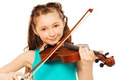 Härlig flicka med långt hår som spelar på fiolen arkivfoto