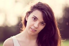Härlig flicka med långt svart hår i trädgården som ser dig Arkivfoton