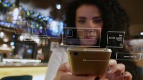 Härlig flicka med lockigt hår i en restaurangbrukssmartphone med den holographic manöverenheten arkivfilmer