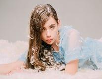 Härlig flicka med ludd i hennes hår som mycket ligger på dunig säng av fjädrar, läggdagsfantasi Ung kvinnlig i blåttklänning Arkivfoton