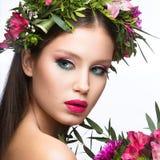Härlig flicka med många blommor i deras hår och ljusa rosa smink Spring avbildar Härlig le flicka Arkivbild