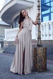 Härlig flicka med mörkt hår i elegant beige klänning Arkivfoton