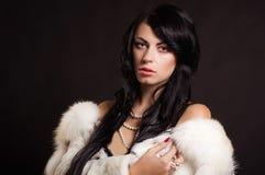 Härlig flicka med mörkt hår i ett vitt pälslag Arkivbild