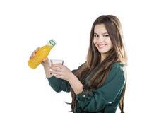 Härlig flicka med mörkt hår som häller från en flaska in i ett exponeringsglas av orange fruktsaft på en vit bakgrund Arkivfoto
