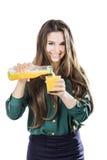 Härlig flicka med mörkt hår som häller från en flaska in i ett exponeringsglas av orange fruktsaft på en vit bakgrund Royaltyfri Foto
