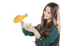 Härlig flicka med mörkt hår som häller från en flaska in i ett exponeringsglas av orange fruktsaft på en vit bakgrund Royaltyfria Bilder