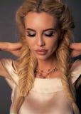 Härlig flicka med makeup för blont hår som och aftonposerar på dubben royaltyfri fotografi