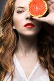 Härlig flicka med orange frukt Arkivbilder