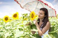 Härlig flicka med paraplyet i ett solrosfält Arkivfoton