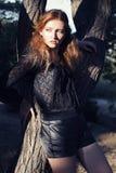 Härlig flicka med rött hår och fräknar som poserar bredvid ett träd Arkivbild