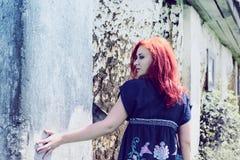 Härlig flicka med rött hår som är utomhus- mot lerahus Royaltyfri Fotografi