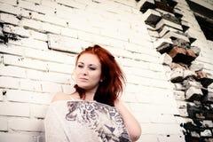 Härlig flicka med rött hår som är utomhus- mot tegelstenväggen Arkivfoto