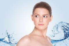 Härlig flicka med ren hud på en bakgrund av plaskande vatten Royaltyfria Bilder
