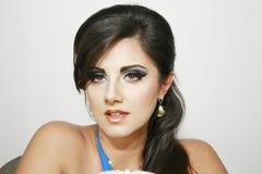 Härlig flicka med romantisk blick, blå intensiv makeup och earings, med långt mörkt hår Royaltyfri Bild