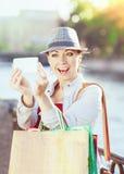 Härlig flicka med shoppingpåsar som tas bilden av henne Arkivfoto