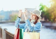 Härlig flicka med shoppingpåsar som tas bilden av henne Royaltyfria Foton