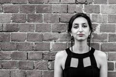 Härlig flicka med svarta örhängen som framåtriktat ser Royaltyfri Foto
