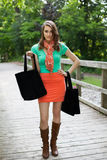 Härlig flicka med torkdukeshoppingpåsar som går på träbron arkivbild
