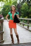 Härlig flicka med torkdukeshoppingpåsar som går på träbron arkivfoton