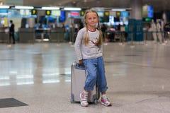 Härlig flicka med två råttsvansar med en resväska på en resa från flygplatsen royaltyfri bild