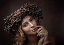 Härlig flicka med vinrankakrans- och blåttdruvor arkivbild