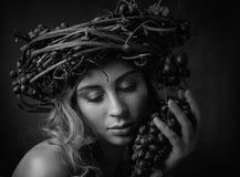 Härlig flicka med vinrankakrans- och blåttdruvor royaltyfri foto