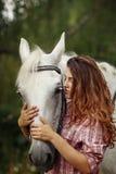 Härlig flicka nära hästen Arkivbild