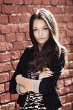 Härlig flicka nära väggen för röd tegelsten royaltyfri fotografi