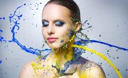 Härlig flicka och färgrika målarfärgfärgstänk Arkivbild