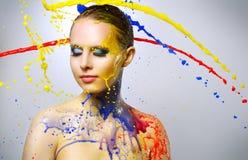 Härlig flicka och färgrika målarfärgfärgstänk Arkivfoto