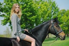 Härlig flicka och häst i vårträdgård Fotografering för Bildbyråer