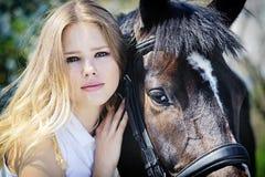 Härlig flicka och häst i vårträdgård Arkivbilder