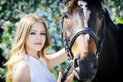 Härlig flicka och häst i vårträdgård Arkivfoton