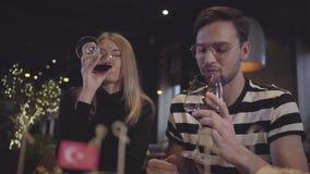 Härlig flicka och trevligt grabbdrinkvin som äter middag i en restaurang Ett par som kopplar av, medan tycka om en bra atmosfär stock video