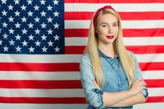 Härlig flicka på bakgrunden av amerikanska flaggan på självständighetsdagen royaltyfri fotografi